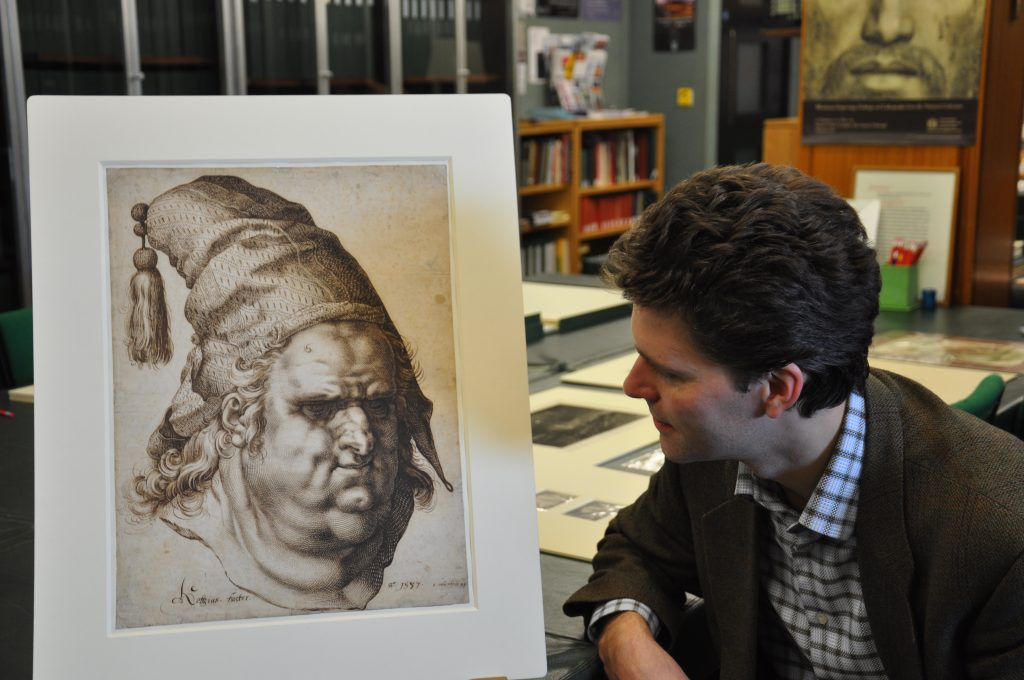 Tico Seifert in front of Hendrick Goltzius' drawing Bust of a Man with a Tassled Cap